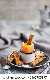 Soft boiled egg with rye toasts for breakfast