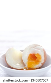 soft boiled egg in white dish place on kitchen cotton cloth