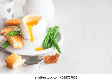 Soft boiled eggs with asparagus and toast soldiers. Copy space background.
