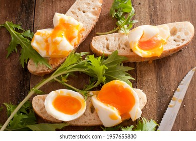 Soft boiled eggs broken open on sliced rolls or baguettes with fresh salad green and a knife while preparing a healthy sandwich