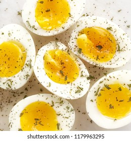 Soft boiled eggs cut in halves with semi-cooked yellow yolk and sprinkled with parsley flakes.