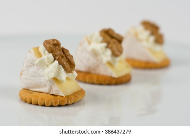Soft brie cheese with crackers and nuts isolated on white, selective focus