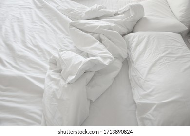 Soft and calm atmosphere image of all white bed room. Pillows and blanket on empty bed, close up.