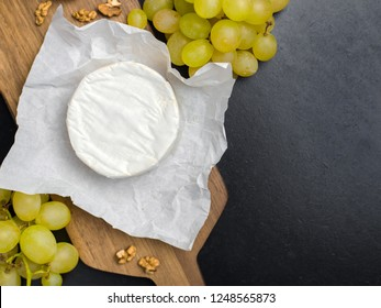 Soft cheese. Camembert and grapes on a wood with nuts.Top view image with copy space