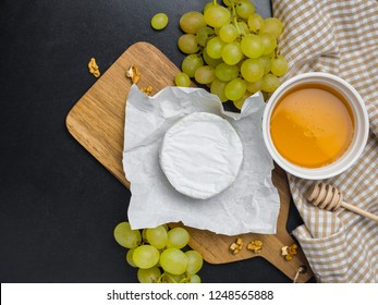 Soft cheese. Camembert, honey and grapes on a wood with nuts.Top view image with copy space