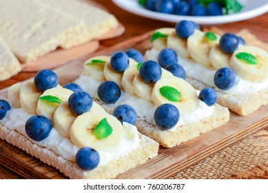 Soft cheese cream, bananas and berries sandwiches. Cracker bread with toppings on wooden board. Closeup