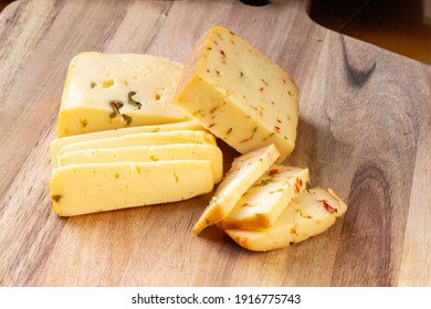 Soft cheese with olives and cheese with chili peppers with tomatoes and rosemary - wood background