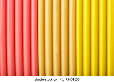 Soft clay from briquettes of pink, beige and yellow for modeling. Plastic colorful material for children art education. Close-up full screen, texture. Harmonious colors