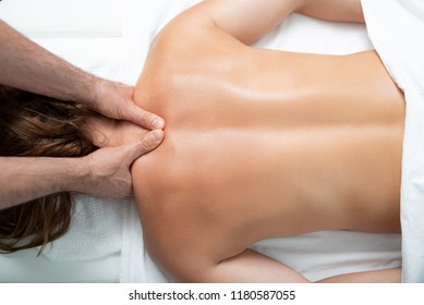 So soft and clean skin. Top view portrait of middle aged woman lying on massage table and receiving body treatment at modern spa salon