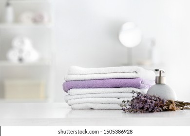 Soft clean towels with soap and lavender on table in bathroom