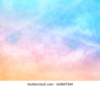 A soft cloud background with a pastel colored orange to blue gradient.  Image features a pleasing paper grain and texture at 100 percent.