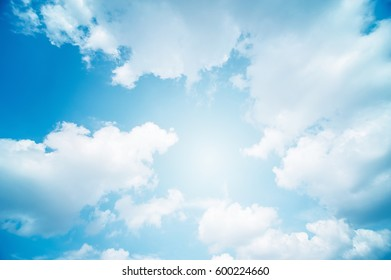 soft clouds and blue sky with sun rays, abstract blue background