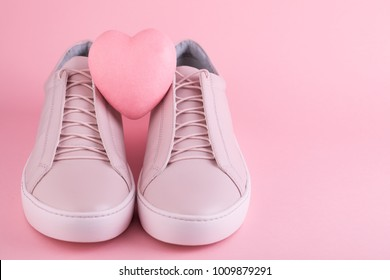 Soft colored women's sneakers on the pink background with heart symbol for the Valentine's Day or Shoe Sale