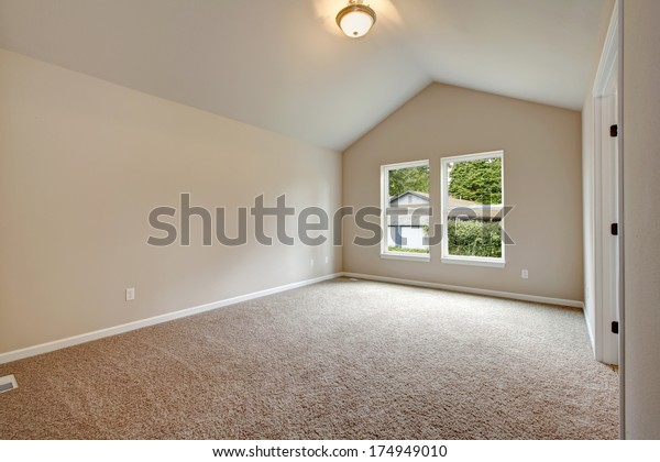 Soft colors empty room with vaulted ceiling, big window, carpet floor