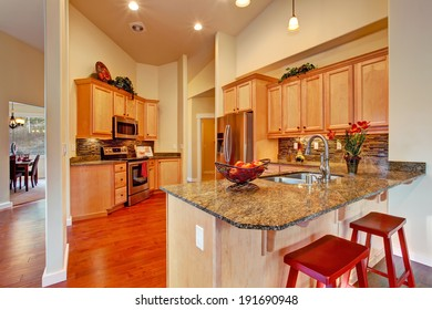 Soft colors modern kitchen area with wooden storage cabinets, steel appliances and tile back splash trim