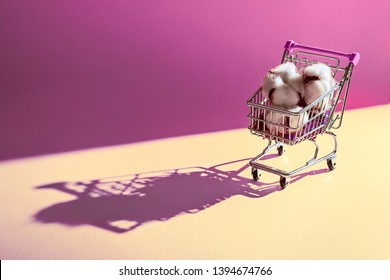 Soft cotton balls sitting in a tiny small shopping cart with dramatic shadows. Cotton represents the fashion clothing industry. Shot in studio.