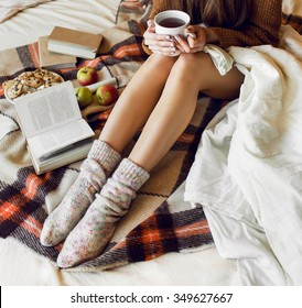 Soft cozy photo of slim tan woman in warm sweater and woolen socks  on the bed with  book  in hands, top view point.  Checkered plaid near  a plate of oatmeal cookies. Fall or winter time  concept.