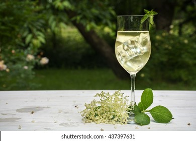 soft drink with ice cubes from elderflower syrup, juice, champagne, soda and mint in a glass on a white wooden table in the garden, selected focus, narrow depth of field