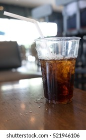 soft drink with ice in takeaway cup on wood table