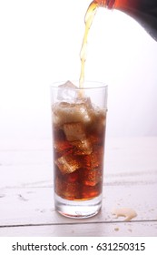 Soft drink poured into a glass with ice.