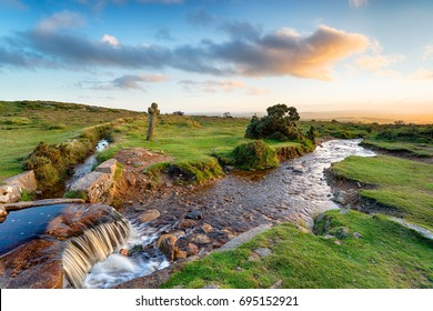 Soft evening light at Windy Post an ancient granite cross overlooking a leat on Dartmoor national park in Devon