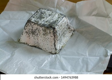 Soft farm cheese made from goat milk with mold and charcoal. Briquette pyramid parallelepiped a piece of cheese in white paper close-up