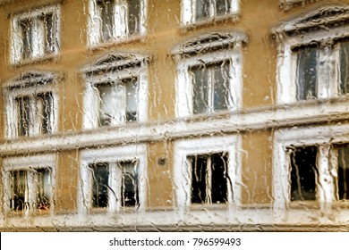 Soft focus in an abstract and watery view through the wet windows of ancient facade of a north european building