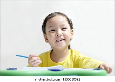 soft focus adorable Asian girl 3 year old sit on her desk. Cute Asia kid smile and look at camera. Kid try to write the book. Concept self learning, Smart and genuine kid, Test examination , happy kid