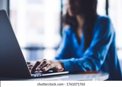 Soft focus of African American female sitting at table in light office and clicking on modern laptop keyboard while working
