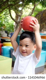 Soft focus at Asian boy holding big red Ceramic Apple over the head and play in the park. The kid try to put big apple on his head. Concept back to school, Arts learning and education, happiness kid.