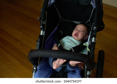 Soft focus of baby crying in the stroller with his feet up