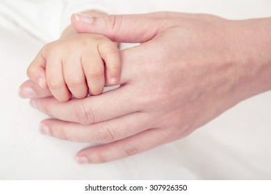 Soft focus of baby hands and mom on the bed, New family and baby healthy concept