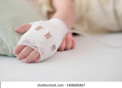 Soft focus at bandage cover on baby hand and Saline intravenous (IV) on hand. Kid sleep on the sickbed in hospital. Concept recovery, Care and love,  Medical treatment, Get well soon.
