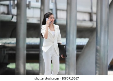 Soft focus of beauty young Asian business woman walking and talking on phone for her job.