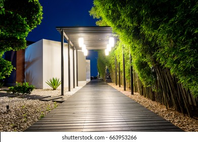 Soft focus of black wooden walk way with bamboo on both side over white pebbles floor at night, Tropical garden path decorative lighting by bulb hung on facade in warm white light.