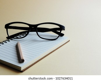 Soft focus blank small notebook with small brown pencil and black glasses on a light yellow table, business planning concept, minimalist