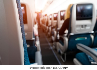 Soft focus and blurred background of passengers on commercial aircraft ,airplane or plane that  airplane cabin interior with seats,air transport is the current popular and fast with lighting.