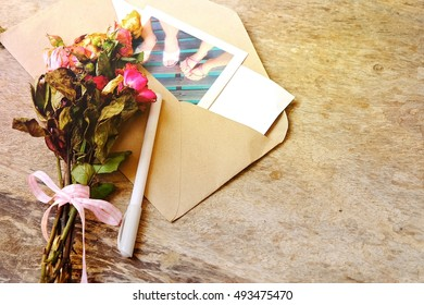 Soft focus and blurry closeup of dry rose flower on wood table. Romantic bouquet of love on wooden background. Retro and vintage style.