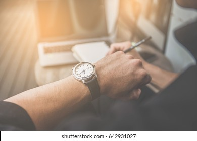 soft focus businessman looking at his watch on his hand, watching the time and writing something on note book.computer laptop on wooden desk