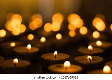 soft focus candle light in darkness on yellow bokeh blurred background atmospheric church interior scene