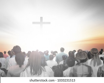 soft focus of christian people group raise hands up worship God Jesus Christ together in church revival meeting with image of wooden cross over cloudy sky can be used for Christian worship background