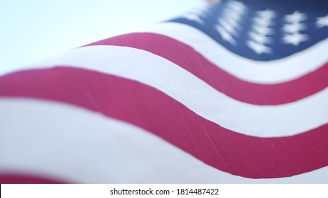 Soft focus close up of American Old Glory flag waving on wind. Stars and Stripes democracy, patriotism, freedom and Independence Day symbol. Star-spangled Banner, national pride and icon of liberty.