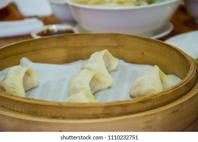 soft focus of close up fresh dumplings with hot steams on a traditional bamboo steamer . Chinese food