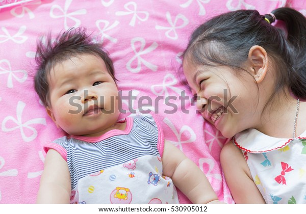 Soft focus Close up Portrait of a sian cute Infant baby  girls with sister