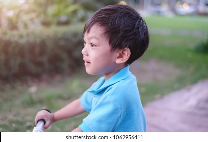 Soft focus and closeup at Asian kid smiling and looking forward. The kid playing in the garden and composing with ray light / Concept of happy kid and happiness life