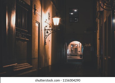 soft focus colorful long exposure concept of backstreet alley way of old european city center district with lantern light and arch corridor under building without people