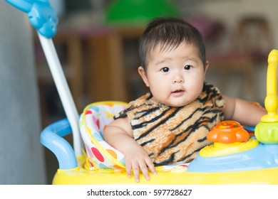 Soft focus Cute Asian male baby sitting on a toy car. Blurred background.