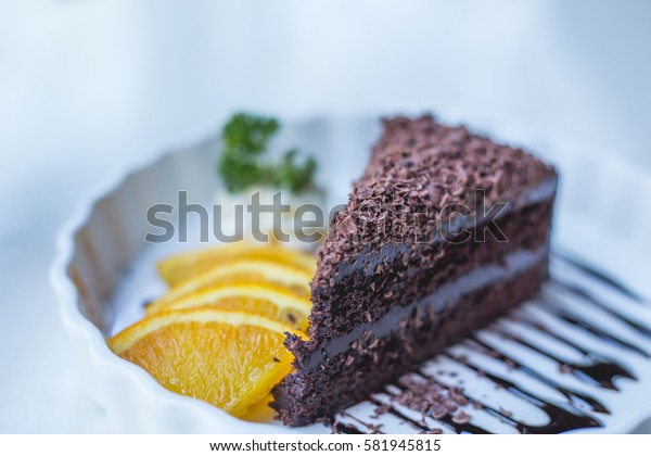 Soft focus delicious chocolate cake on white plate with citrus, closeup.