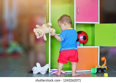 Soft focus, Development of Baby aged of 9 months concept,A little asian child baby boy play with many toys in cabinet. He practice to standing and walking.