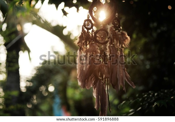 Soft focus Dream Catcher with a flare from the sun set on the background bokeh nature. Native american dream catcher. (Vintage style) boho chic, ethnic amulet.